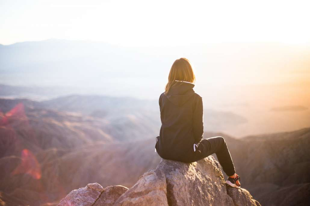 woman doing mindfulness meditation in front of a mountain vista