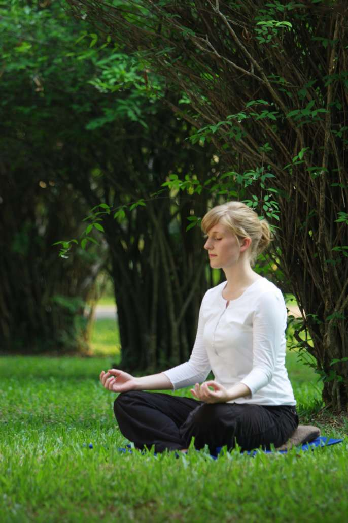 women practicing authentic mindfulness meditation in lotus position
