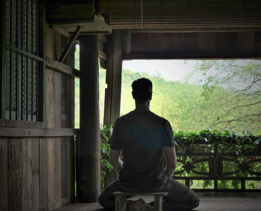 Nicolas practicing minfulness meditation in traditional cambodian house in kep