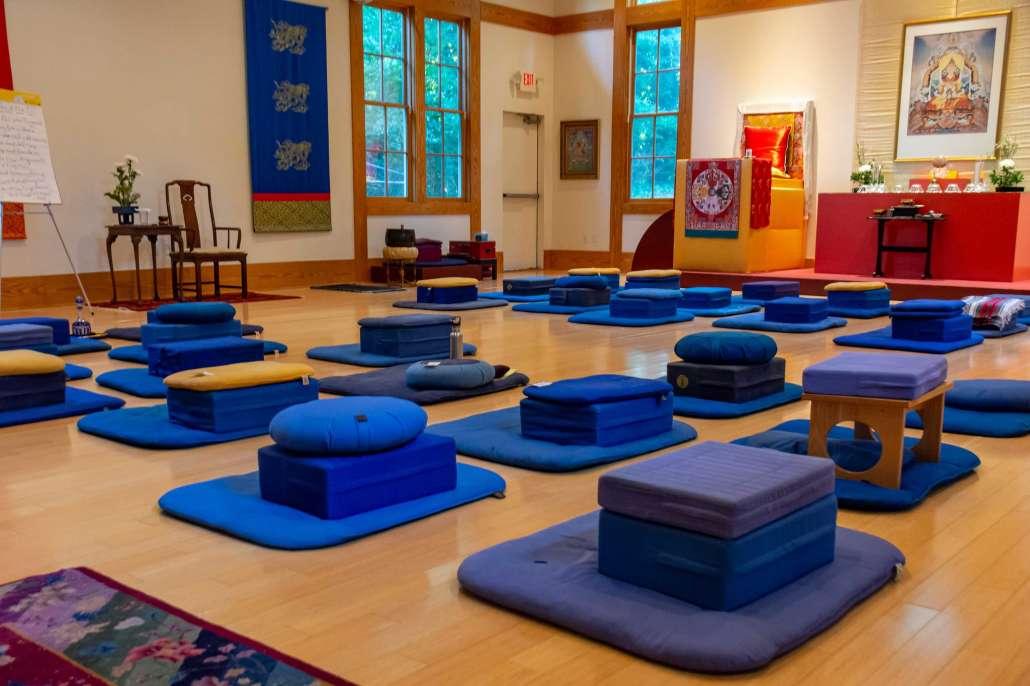 Coussins et sièges de méditation dans une salle de pratique de tradition tibétaine