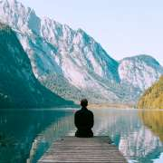 person meditating in a meditation posture in front of a contemplative lake