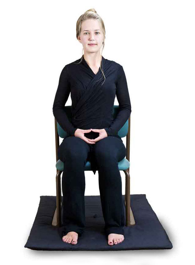 Women meditating in a seated position in a chair